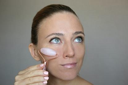 Beautiful woman using pink Jade rose Quartz facial Roller. Skin treatment.