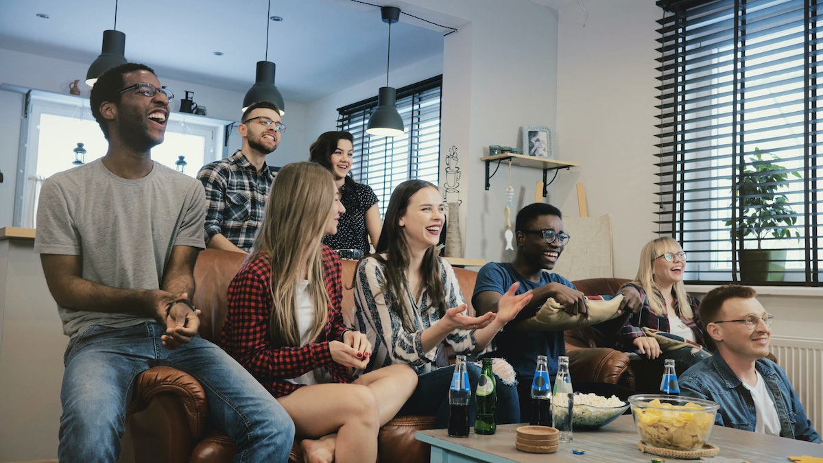 A group of friends sit around with snacks and beer while watching the football game on the couch.