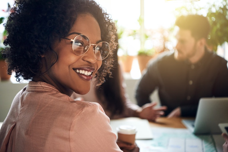Smiling African businesswoman looking over her shoulder while sitting at a boardroom table with colleagues working in the background