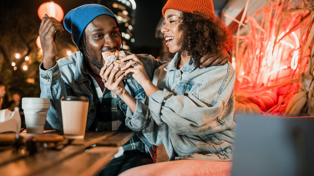 A trendy couple in beanie caps enjoy each other's company at a coffee shop.