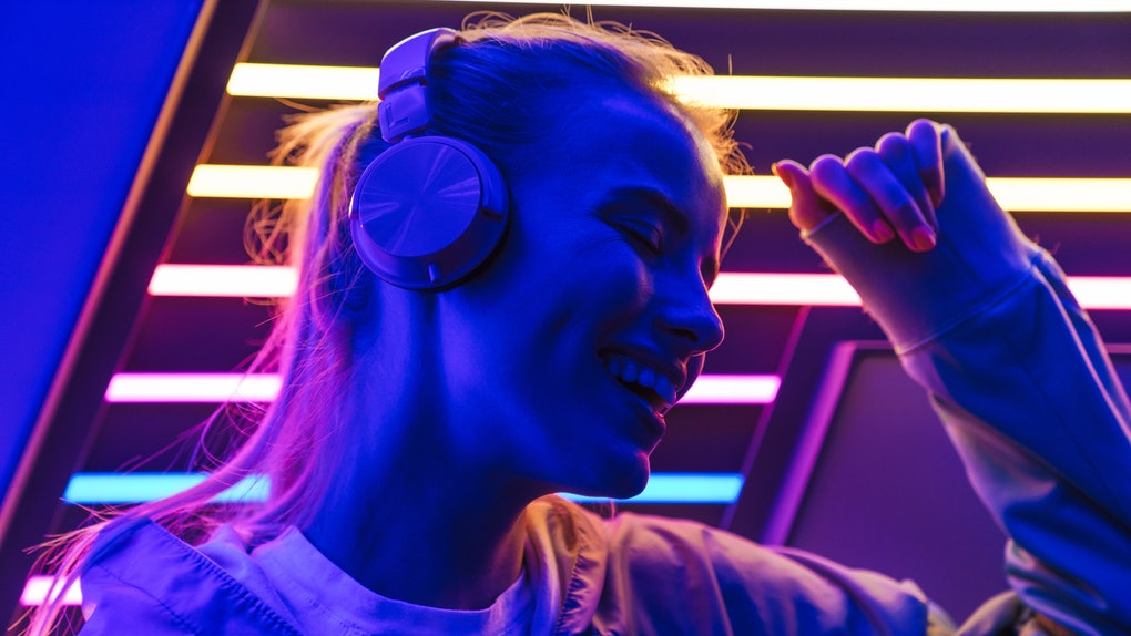 Image closeup of beautiful young caucasian woman listening to music with headphones over multicolored neon lights