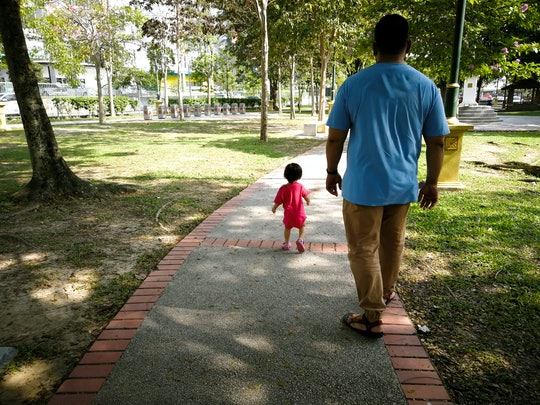 Asian father and baby toddler daughter walking in the park.
