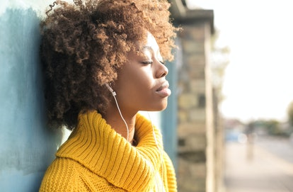 Beautiful girl relaxing listening music in the street
