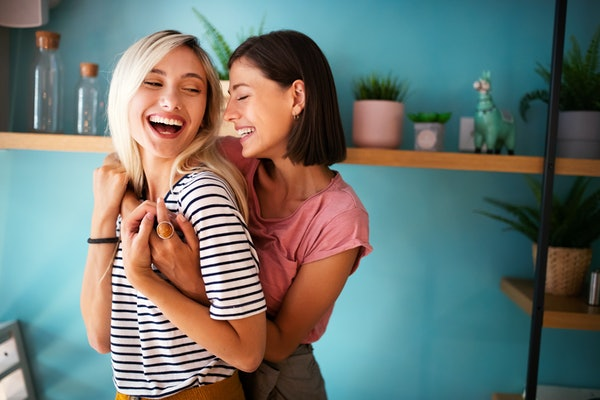Two women smile and embrace in a blue room on a sunny day.
