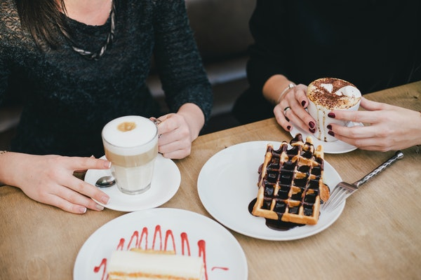 A close-up of two women's hands holding their coffee cups on a table next to plates of waffles.