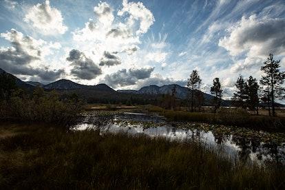 A pond reflects the sky and the sun slowly setting near Lake Tahoe, south of Tahoma, California, USA...
