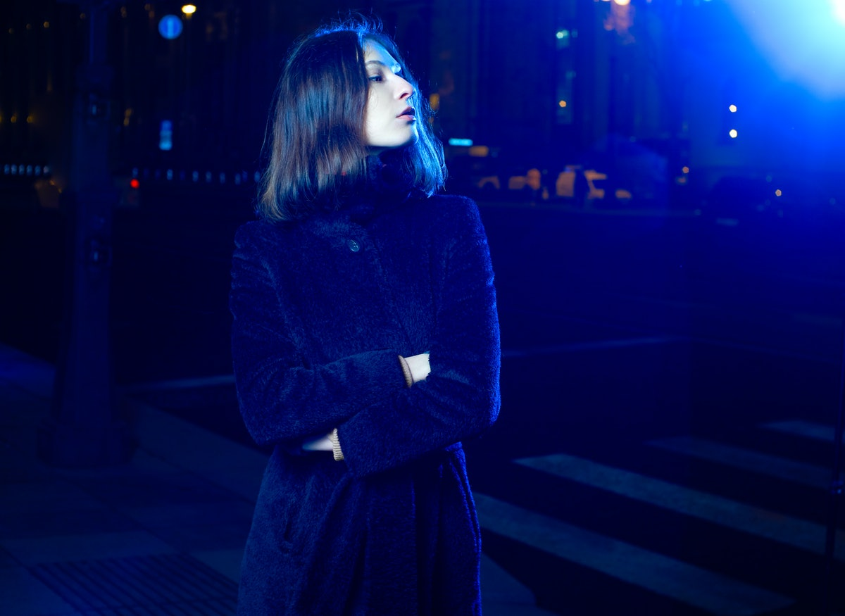 Fashion portrait girl in the night city and lights of street lamps. in the coat. illuminated by a blue lantern.