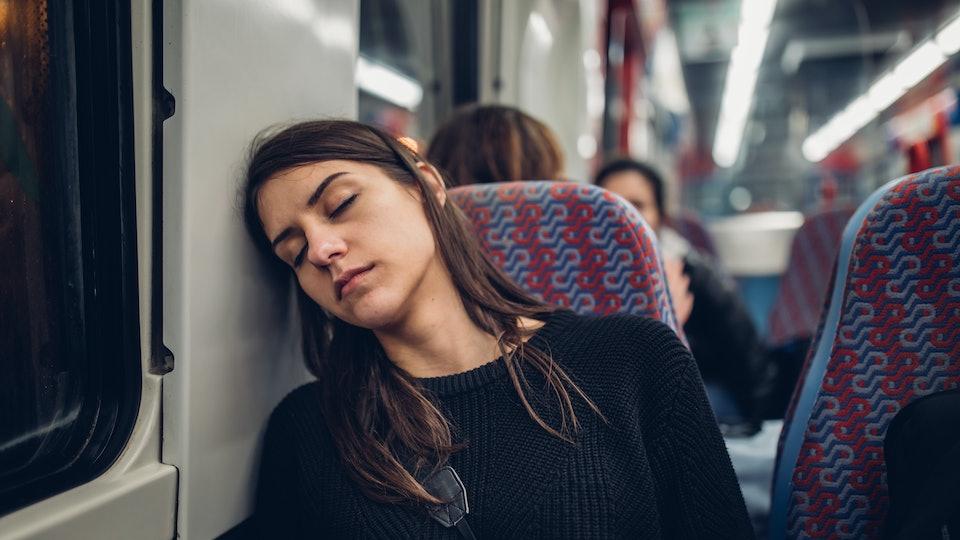 exhausted woman sleeping on train