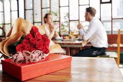 Horizontal shot of beautiful red roses and box of chocolate lying on cafe table, couple dating on ba...