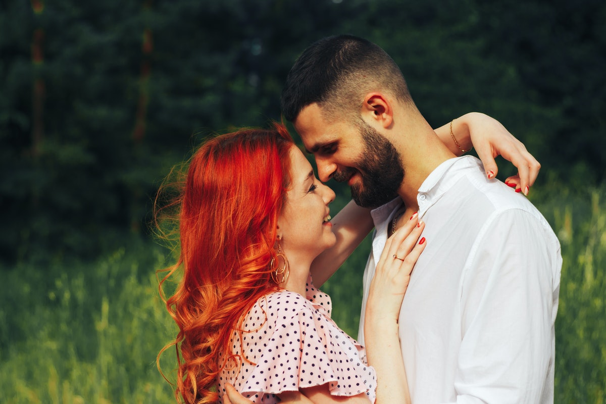 A woman with red hair hugs her boyfriend and smiles in a sunny field.