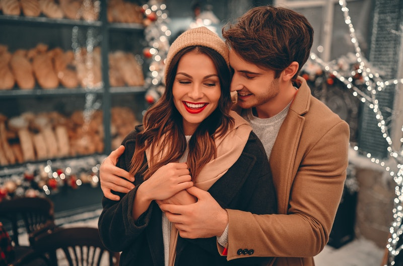 Young romantic couple is having fun outdoors in winter before Christmas. Enjoying spending time toge...