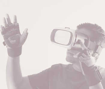 Young handsome man wearing virtual reality goggles touching controls to shoot in game