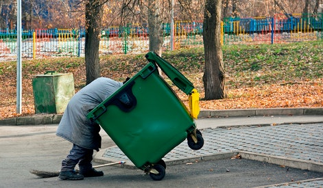 Man digs in the trash. Homeless and jobless person