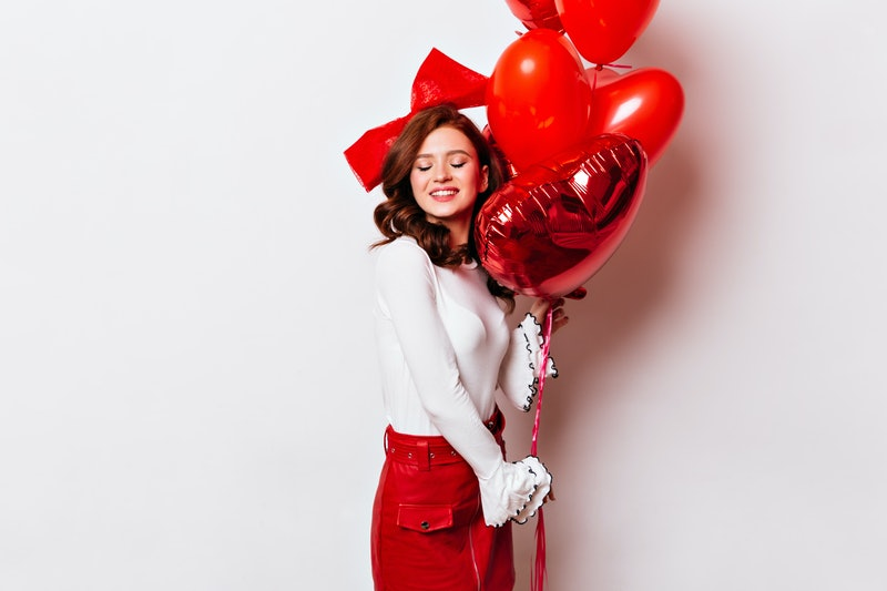 Happy ginger girl posing after date. Studio shot of european female model with red heart balloons.
