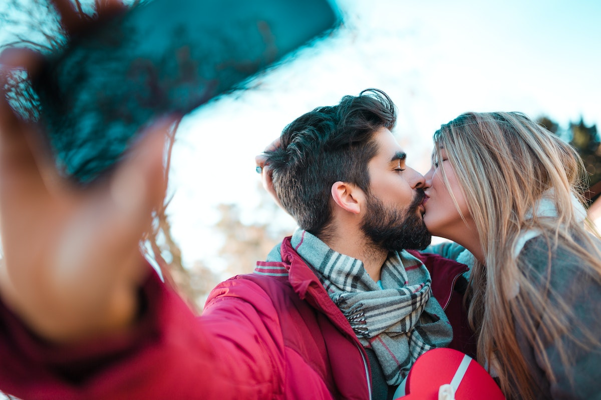 A couple kisses and takes a selfie while holding a box of chocolates on Valentine's Day.