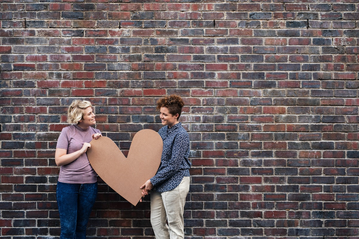 A happy couple holds up a large cardboard heart in front of a brick wall.