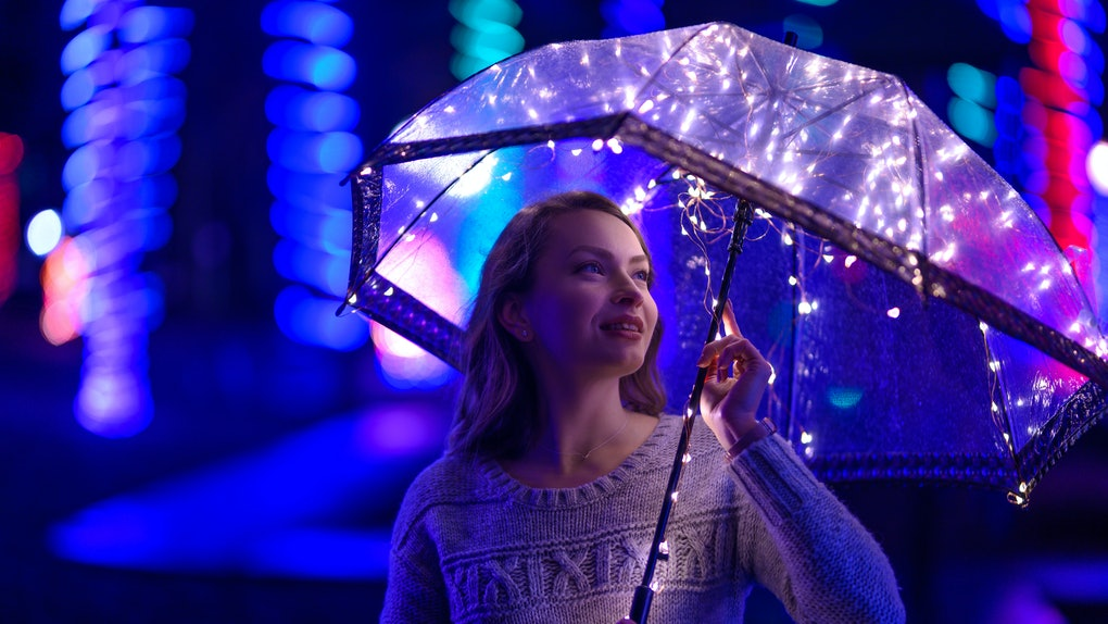 A girl walks through the night city with lights. Rainy. With an umbrella with lights.
