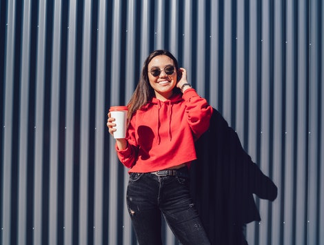 Half length portrait of happy smiling female student standing near copy space area for advertising text and looking at camera on leisure, young chinese hipster girl with coffee to go posing outdoors