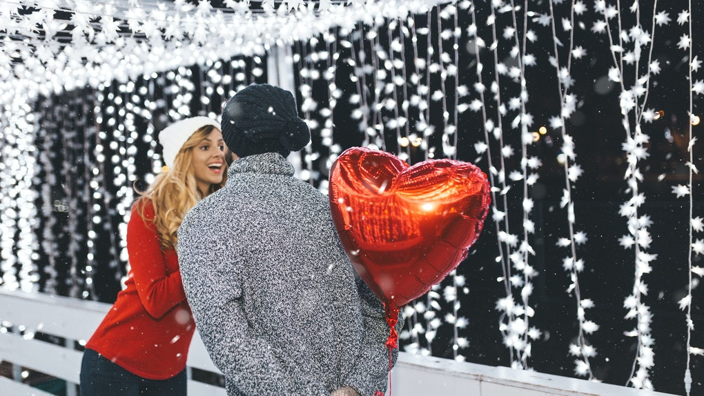 A woman smiles at her boyfriend who's holding a heart-shaped balloon behind his back on the ice rink.