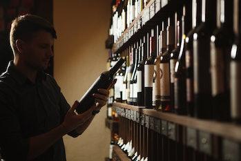 man choosing bottle of wine from shelves