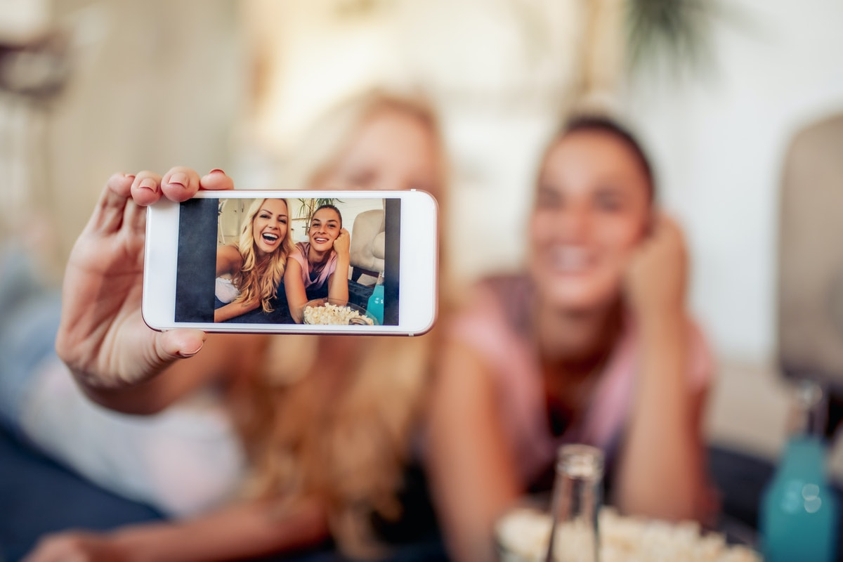 Two girl friends hold a bowl of popcorn and snap a selfie on the couch.