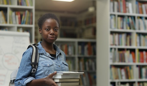 Portrait of African young woman looking at camera while holding heap of books in her hands in the library