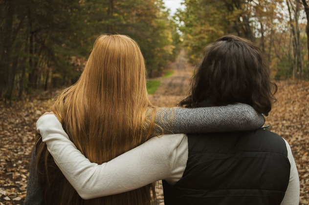 Two college age girls in the woods with a path ahead of them with arms around each other. Season is fall.