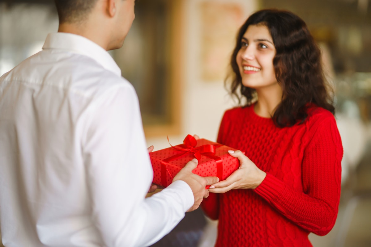 Man gives to his woman a gift box with red ribbon. A loving couple cuddles and celebrating Valentine's Day in the restaurant. Valentine's Day, holiday and surprise concept. Relationship and love.
