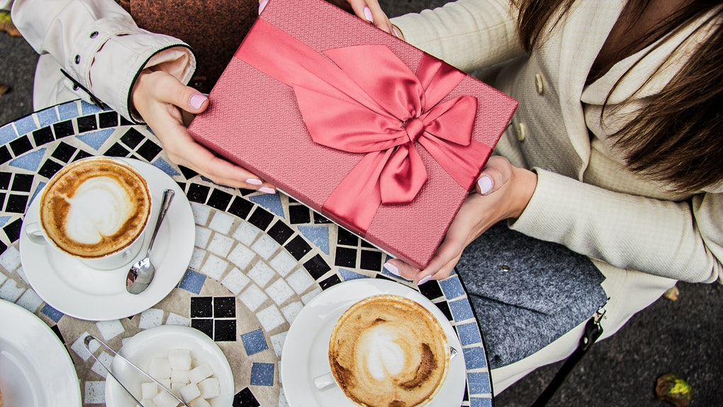 Top view of a woman giving her friend a pink present at a mosaic coffee table.
