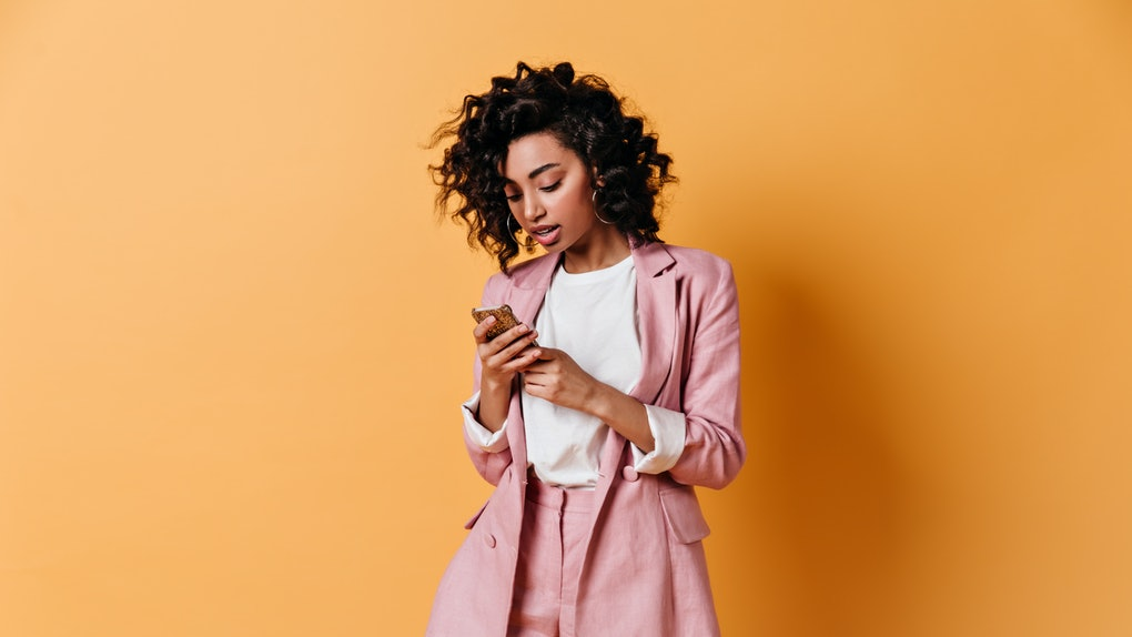 Focused curly woman texting message. Studio shot of elegant girl holding smartphone on yellow background.