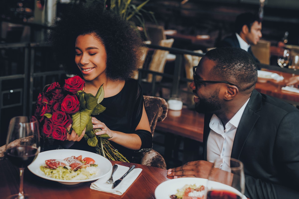 A woman holds a bouquet of red roses at a restaurant that her boyfriend gave her on Valentine's Day.