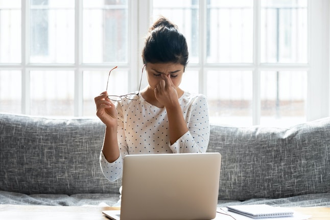 Tired young woman take off glasses massage eyes overwhelmed with computer work have blurry vision, exhausted millennial girl worker suffer from migraine or headache, struggle with dizziness