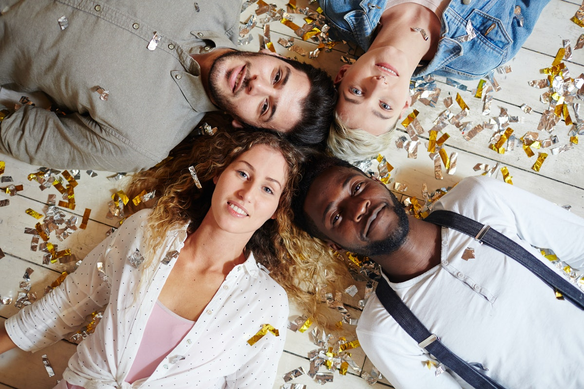 Two restful couples lying head by head on the floor after party