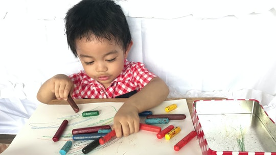 toddler boy playing with crayons