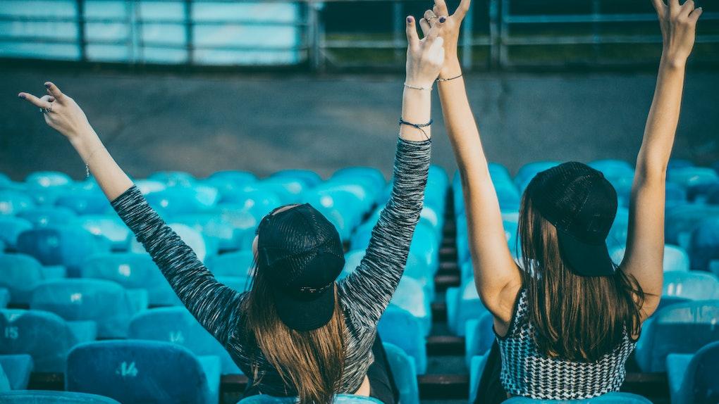 Two women wearing backwards baseball caps cheer on their team in the bleachers.