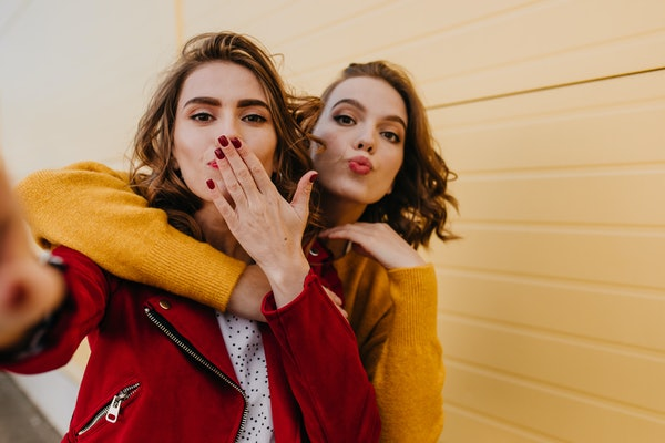 Two women blow a kiss at the camera while posing for a selfie outside.