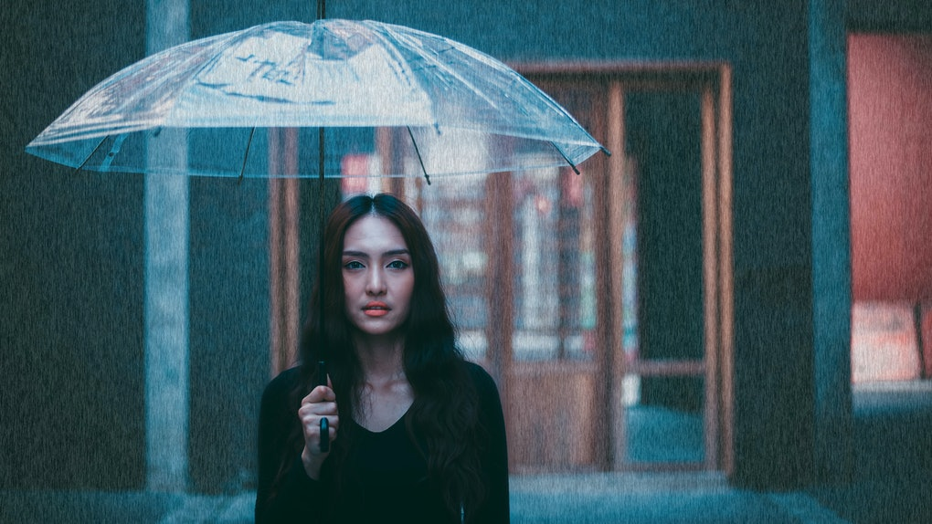 Portrait charming beautiful woman. Attractive beautiful woman is looking at walking street. Gorgeous girl holds umbrella because it's nearly raining. Glamour lady is walking around the city or town.