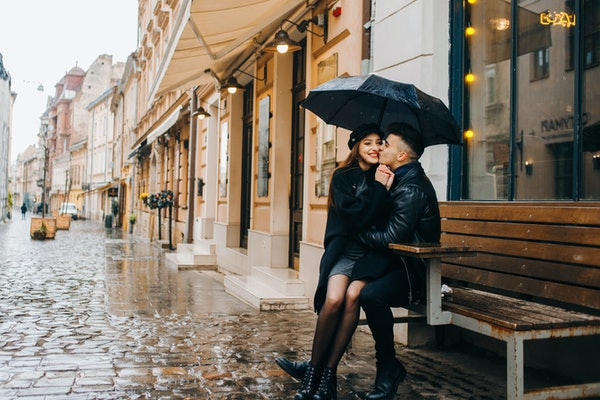 A girl smiles and sits on her boyfriend's lap under an umbrella on a rainy afternoon in a city.