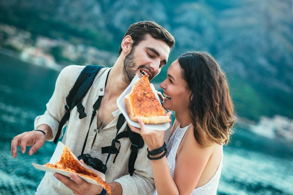 A happy couple who's traveling enjoys a slice of pizza by the water.