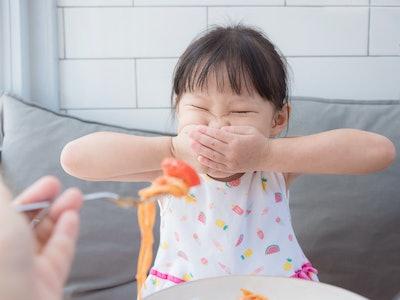 a little girl refusing to eat spaghetti