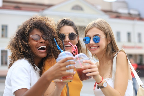 Three trendy girls in sunglasses toast their smoothies and smile on a sunny day in the city.