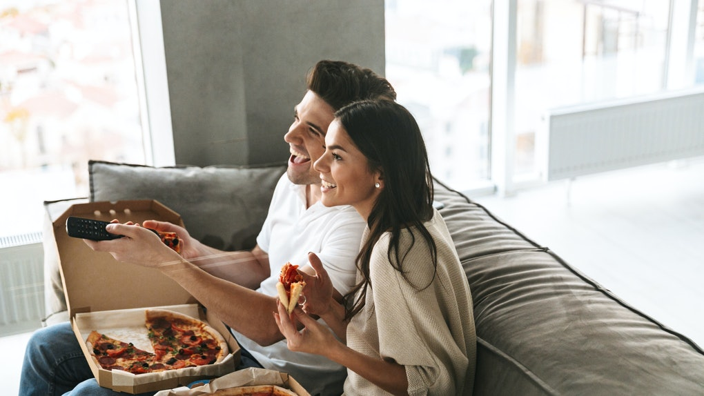 A young couple enjoys pizza on the couch and watches TV.