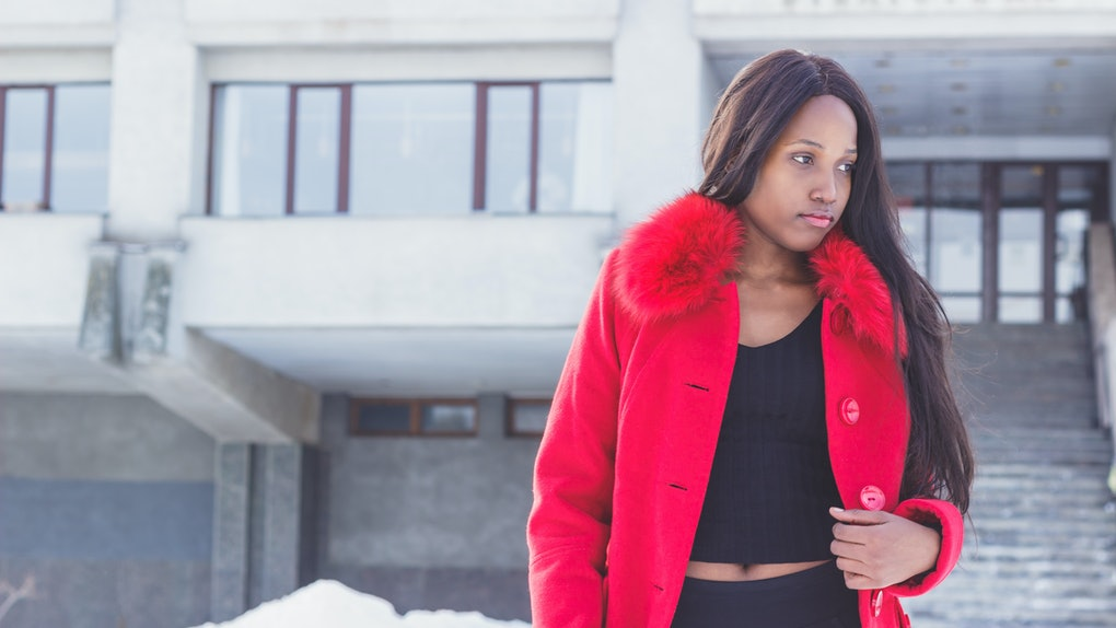 Winter life: Young African woman in a red coat, black pants and sweater.