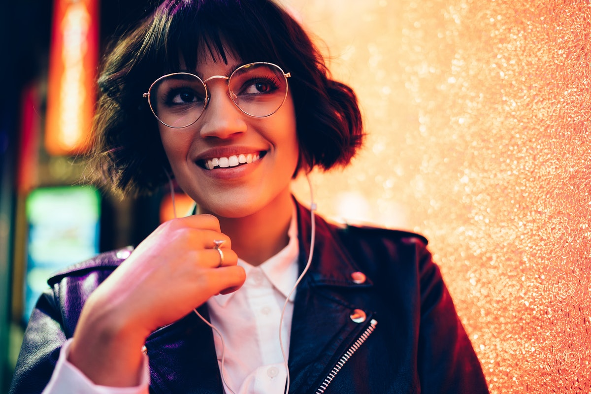 Dreamy pretty hipster girl in stylish lather jacket and fashionable eyewear listening electronic audio songs from playlist in modern earphones outdoors on New York street with night lights