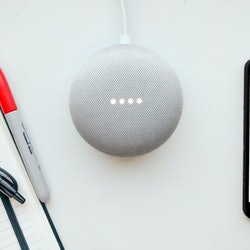 Digital Assistant concept. Flat lay of smart speaker, blank smartphone and notepad. LED lights activated.