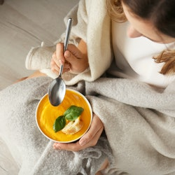 Woman eating tasty cream soup at home