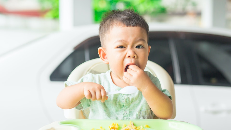a toddler boy eating eggs in his high chair
