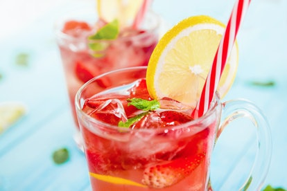 Colorful refreshing drinks for summer, cold strawberry lemonade juice with ice cubes in the glasses garnished with sliced fresh lemons