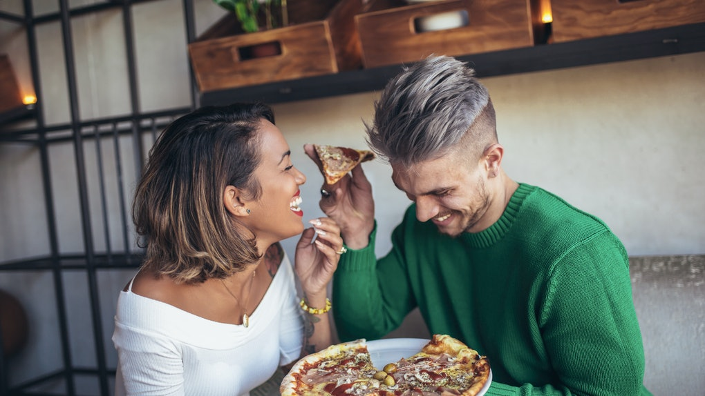 A couple laughs and eats pizza on a couch in a modern living room.
