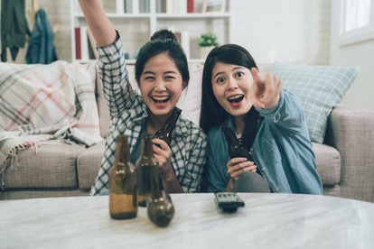 two excited asian women cheerful laughing celebrating victory win watching games on television tv po...